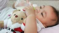 Baby Bottle Feeding , hold Santa doll