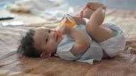 Baby junge trinkt Orangensaft.