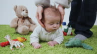 MS Baby boy (2-5 months) lying on stomach on carpet amongst toys, Brussels, Belgium
