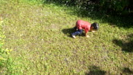 Baby boy running and fall down on wet grass.