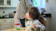 Baby boy sitting in high chair eating breakfast, parents in background