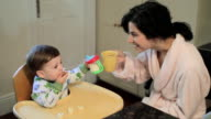 Baby boy sitting in high chair eating breakfast with mother