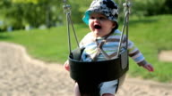 Baby Boy Sitting in Playground Swing Outdoors Slow Motion