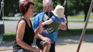 Baby Boy Sitting in Playground Swing Outdoors With Grandparents