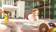 A baby crawling towards the camera with her toys and games around her.