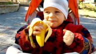Baby eating banana in park