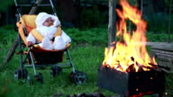 Baby falling asleep in front of the campfire