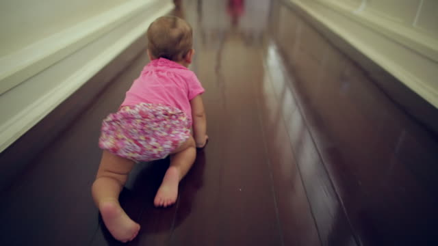 TS baby girl crawling down a hallway at home.
