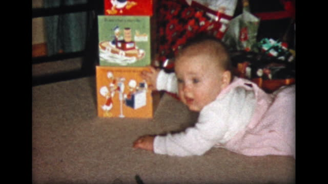1957 baby girl crawls near presents under Christmas tree