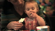 MS Baby girl (12-17 months) eating icing off cupcake with her hands sitting on mother's lap / Norwich, Vermont, USA