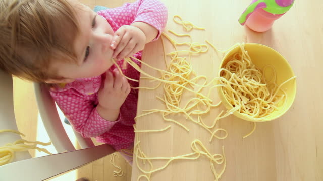 MS HA Baby girl (12-23 months) eating pasta at table / Jersey City, New Jersey, USA