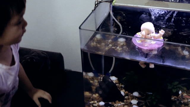 Baby Girl Exciting With Fish In Aquarium Tank