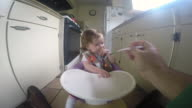 A baby girl feeding while sitting in a chair inside of her house.