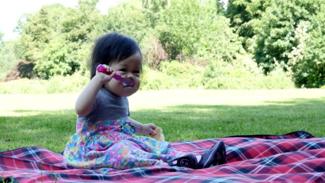 babymeisje heeft picknick in de zomertuin