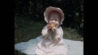 1940 - baby girl in garden biting a tomato