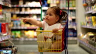 baby girl in shopping cart sitting and demanding
