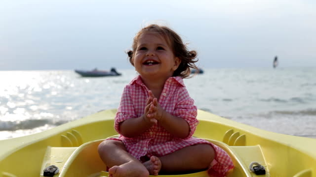 Baby girl is sitting in a yellow canoe and feeling ecstatic, smiling, clapping and enjoying, have fun