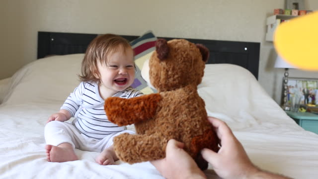 A baby girl laughing and having fun on a bed inside a home.