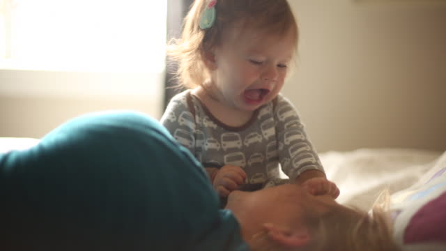 A baby girl laughing and smiling with her mom on a bed indoors.