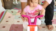 A baby girl playing and riding on a toy bike outdoors.