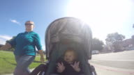 A baby girl riding in a stroller on a sunny day near a Farmers Market and lake.