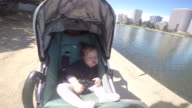 A baby girl sleeping in a stroller on a sunny day near a Farmers Market and lake.