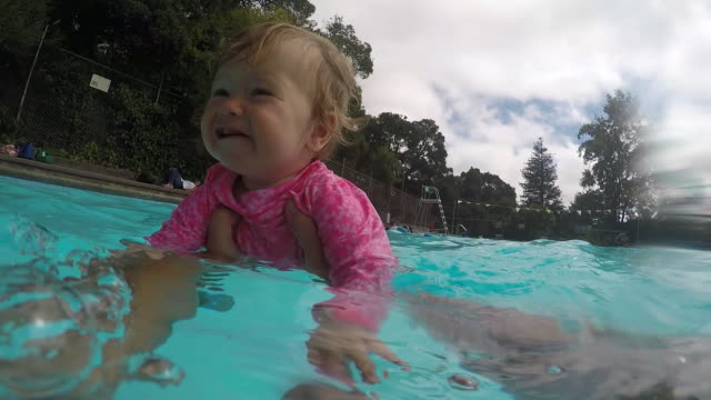 A baby girl swimming in the arms of her father outdoors inside of a pool on a sunny day.