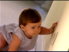 Baby girl touching electrical outlet
