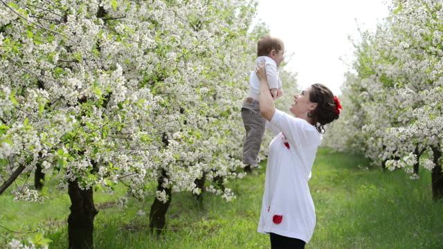 Baby held in seiner Mutter in der Wiese