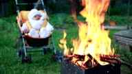 Baby in the pram sitting in front of the campfire