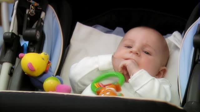 Baby in the pram sucks thumb - medium shot