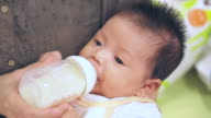 Baby infant suckling milk from bottle