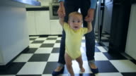WS TS Baby learning to walk with help from her mother.