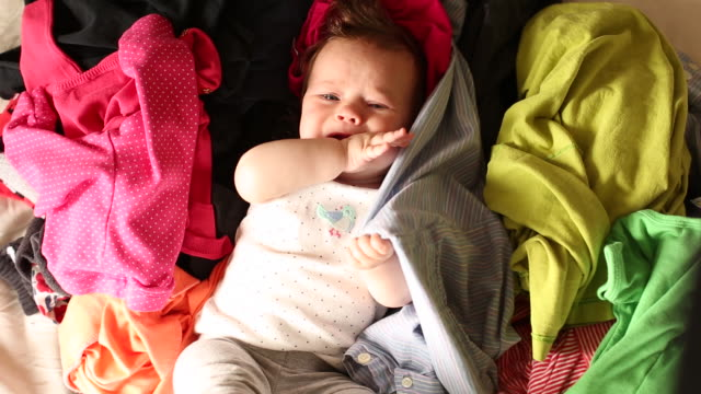 A baby lying on her back on top of a pile of clothing.