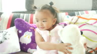 Baby playing with fluffy doll