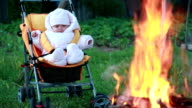 Baby sitting in the pram in front of the campfire
