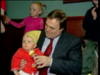 Baby sitting on knee of Deputy Prime Minister John Prescott CS Baby PULL OUT with Prescott as he jokes about the baby putting a fist to his face SOT...