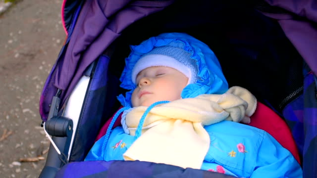 Baby sleeping in a carriage outdoors