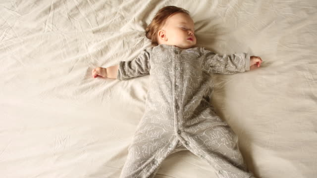 A baby sleeping on a bed in her pajamas inside of a home.