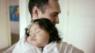Baby sleeping on father in nursery