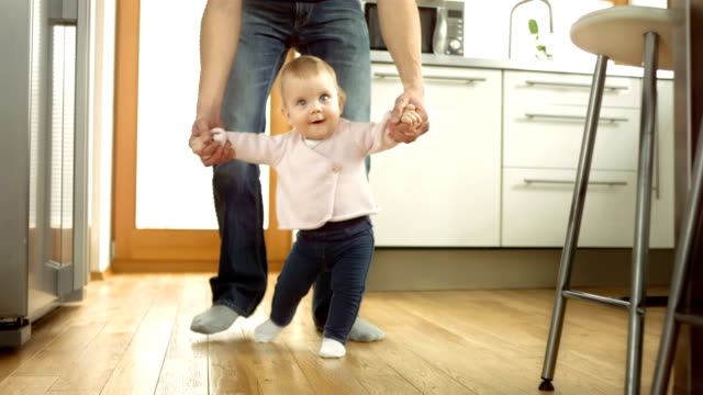 Baby Taking First Steps With Father's Help