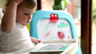 Baby toddler playing with a digital tablet in high chair