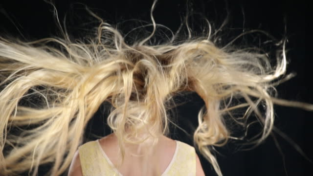 MS SLO MO Back of woman with long blond hair moving in wind,woman turns around and smiling / London, Greater London, United Kingdom