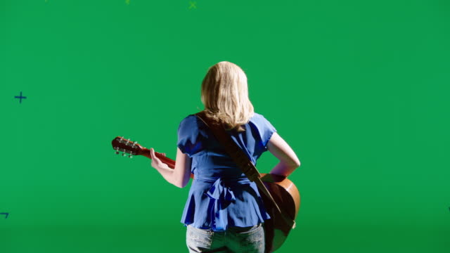 MS Back of women singing and playing the guitar in front of green screen