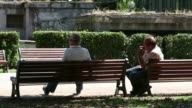 Back views two men sit on a park bench in the sunshine as pedestrians walk past in Rome Italy on Friday July 11 A man sits reading a newspaper on a...