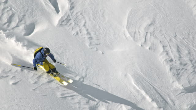 SLO MO Backcountry skier skiing down slope in powder snow