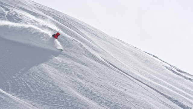 SLO MO Backcountry snowboarder riding down the sunny mountain slope