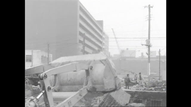 A backhoe dumps rubble into a dump truck at the construction site of the Tokyo's Nishi-Shinjuku district.