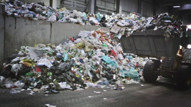 CS Backhoe loader loading the garbage onto a conveyor belt