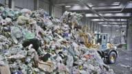 LD backhoe loader piling up plastic waste